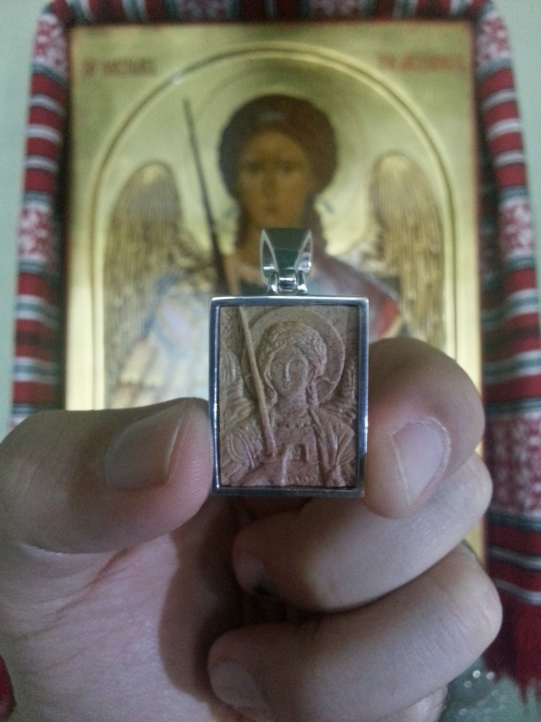 Holy St. Michael the Archangel pendant by Jonathan Pageau in the foreground aligned with the icon painted by Anna Gouriev in the background.