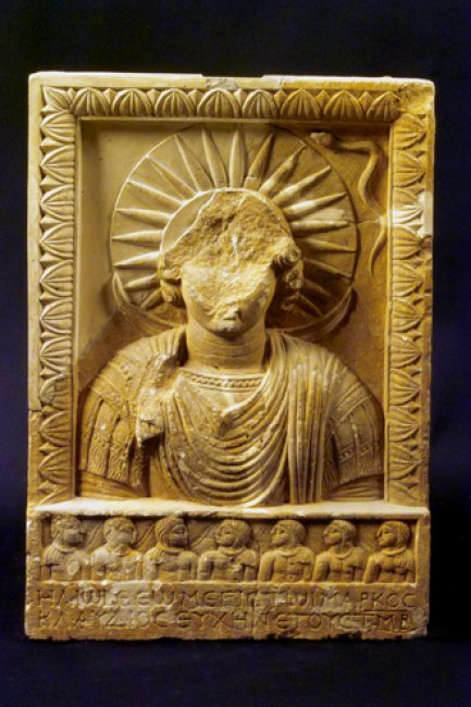 """Deity Helios, embossed stone panel. Syria, 2nd Century. Comment: In this work we see a prefiguartion in Paganism of Christ,""""The Sun of Rightousness"""" and """"Light of Life."""" This work looks forward to the Incarnation and is meant to functions as an embodiment of the Sacred. Hence, the """"iconic"""" qualities of this stone relief are clearly evident. Notice the halo, a symbolic feature which will become indispensable in the future development of Christian iconography."""