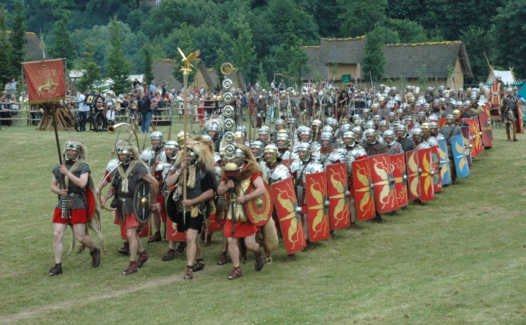Historical reenactors dressed as Roman soldiers bearing vexilla and aquila.