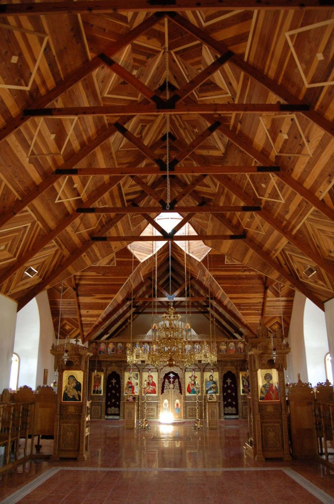 Modern Greek iconostasis at St. Anthony's Monastery, Arizona. The dark carved wood looks dull and indistinct from a distance, and in dim light, so the iconostasis fails to achieve visual dominance. In contrast, the bold parquetry patterns in the wooden ceiling are highly legible, and the are clearly the dominant.