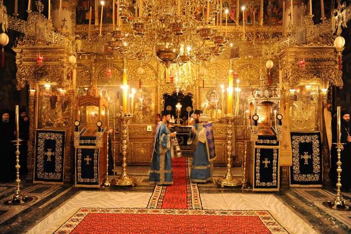 A carved and gilded iconostasis has such presence that it can maintain visual dominance even when crowded behind furniture and lamps. Hilandar, Mt. Athos.