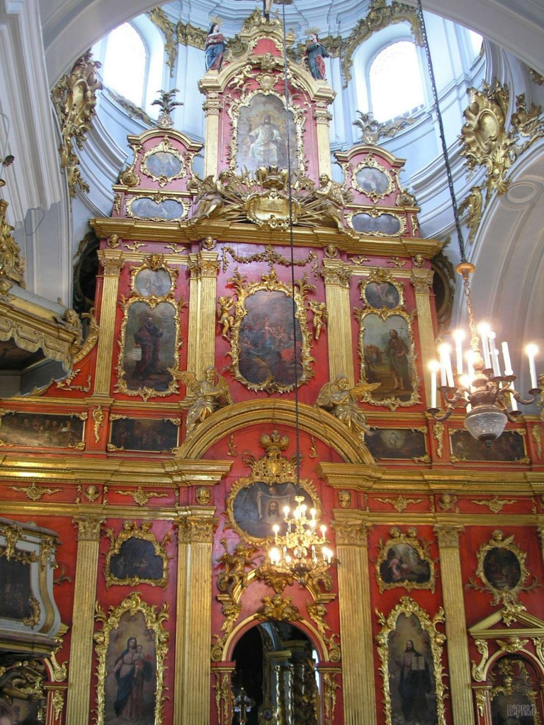 A late-Baroque iconostasis, St. Andrew Cathedral in Ukraine. This screen represents the low-point of iconography, where it has been reduced to small western-style paintings of an almost purely decorative nature. But the screen itself, painted fiery red and gilded, still conveys much of the divine symbolism and liturgical ethos of earlier screens. This goes to show the value of a magnificent screen, and its ability to work wonders for a church, even if the icons it holds are of little merit.