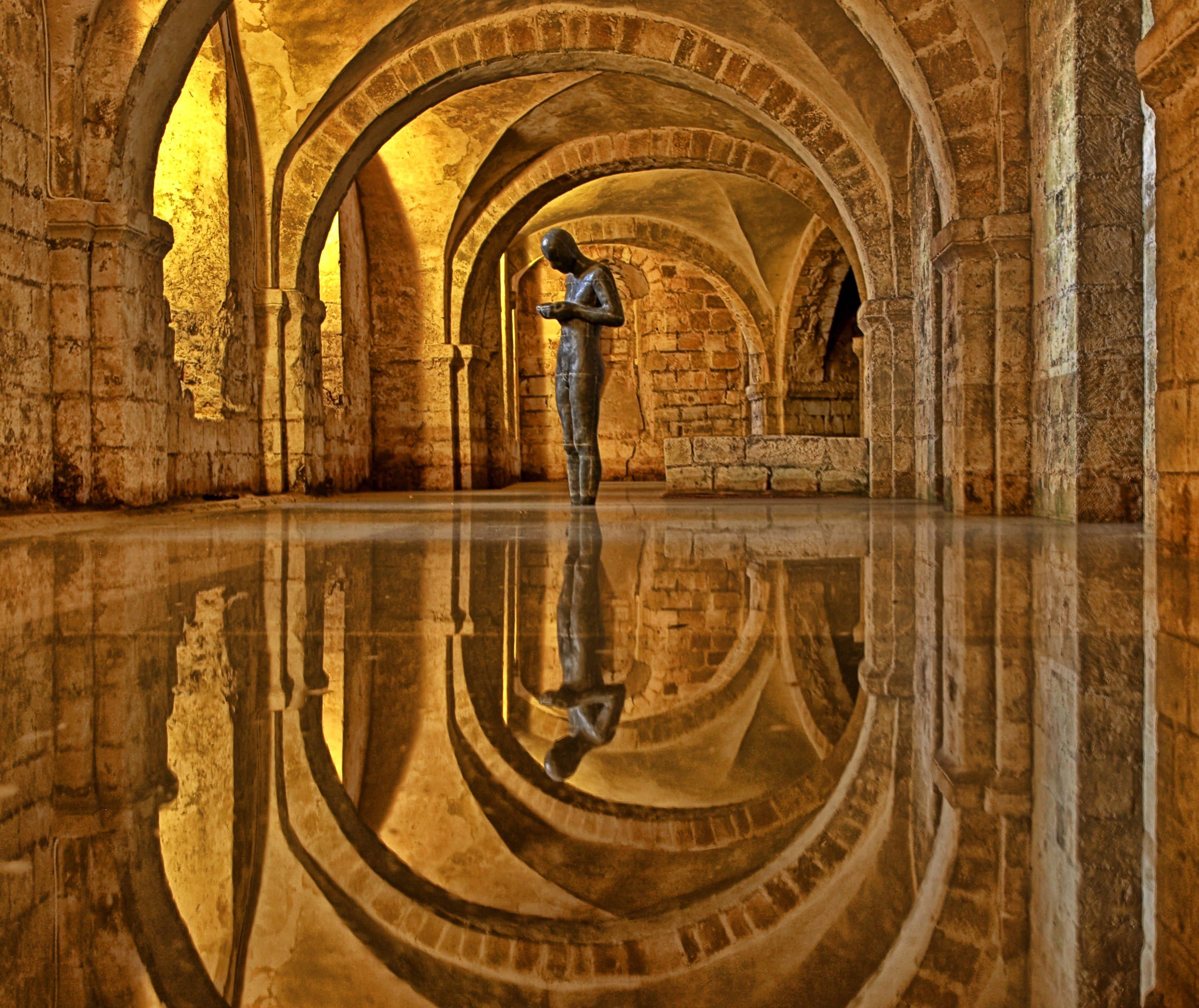 Antony Gormley, Sound II, 1986. Sculpture, metal statue standing in flooded crypt, Winchester Cathedral, England, UK.
