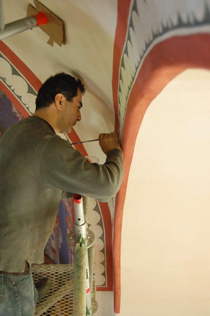 Aleko painting decorative borders on the pendentives.