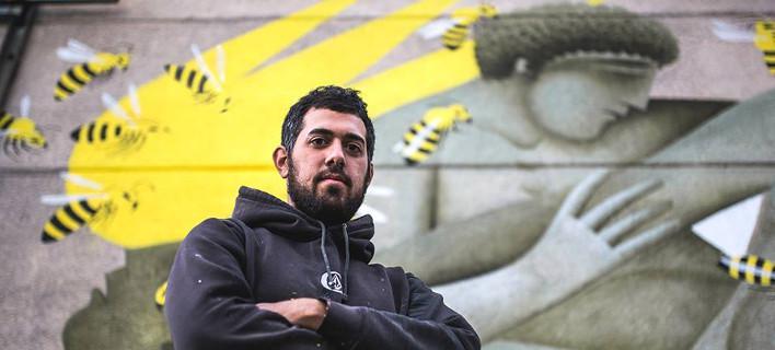 Fikos in front of one of his murals.