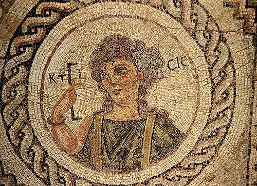 """Ktisis (Creation) holding a measuring rod. A nearby Inscription reads: """"This house…has now girt itself with the much venerated symbols of Christ."""" House of Eustolios, Kourion, Cyprus. Floor Mosaic 5th Century."""